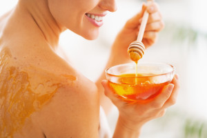 Closeup on young woman with honey on back holding honey plate