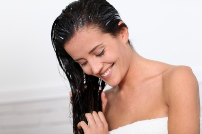 Beautiful woman applying hair conditioner